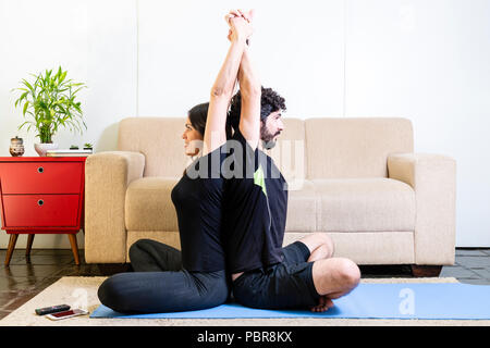Beautiful hetero caucasian couple in black clothes on blue yogamat doing sit back-to-back pose with arms up - Stock Photo