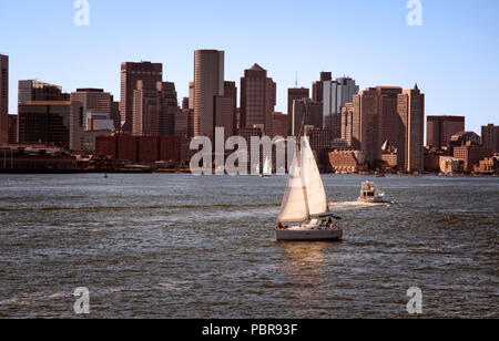 Boats cruising in Boston Harbor as the sun starts to set with the Boston skyline of buildings along the shore. - Stock Photo