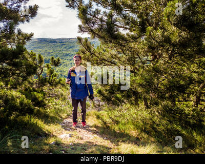 portrait of young man photographer in the mountain forest looking on landscape panorama and make photo with camera - Stock Photo