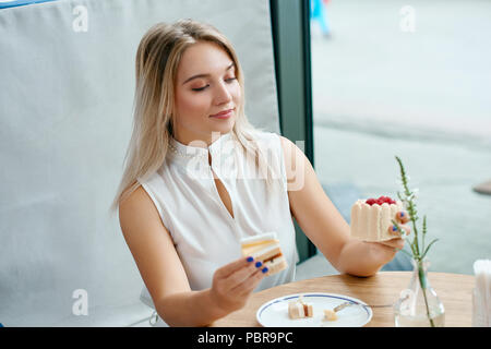Pretty blonde girl can't choose between two delicious cakes. Keeping tasty desserts in both hands, looking on piece of raspberry cupcake with creame. Sitting on wooden table. - Stock Photo