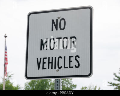 No motor vehicle sign in park with a USA flag on background - Stock Photo