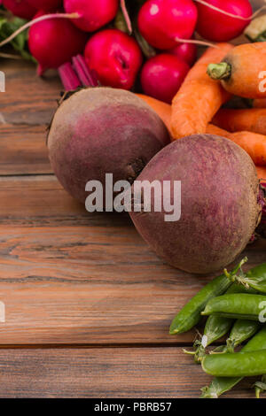 Beetroots, peas, carrots and radish on wooden table. Close up. Fresh ripe homegrown vegetables. - Stock Photo