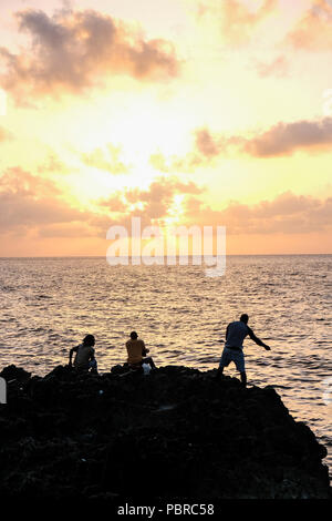 Caymanians people fishing from shore at sunset Cayman Island - Stock Photo