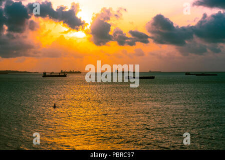 The sun begins to set over the waters of the Panama Canal. - Stock Photo