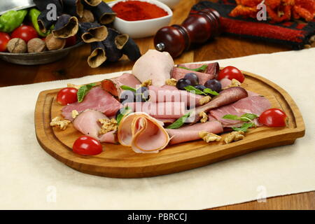 Ham, salami and bacon on wooden plate - Stock Photo