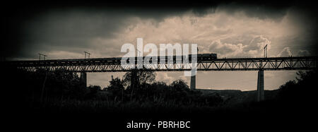railroad train moves along the bridge against a background of thunderclouds and clouds. Horizontal web banner. - Stock Photo