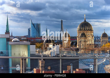 Urban view over the rooftops of the old town Riga, with the chimneys and spires of cathedrals and churches in the beautiful evening light - Stock Photo