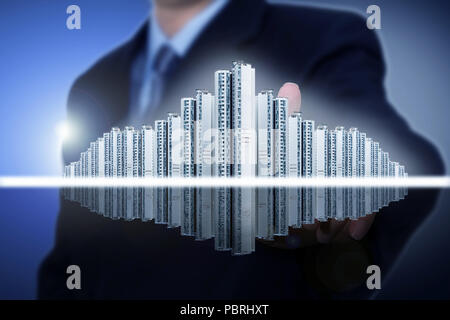 Businessman touching model house with finger - Stock Photo