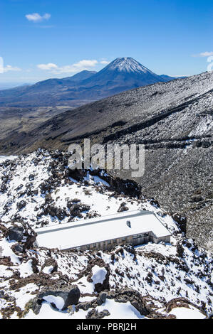View from Mount Ruapehu on Mount Ngauruhoe with a ski cottage in the foreground, Unesco world heritage sight Tongariro National - Stock Photo
