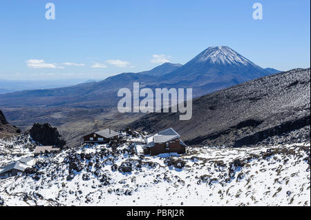 View from Mount Ruapehu on Mount Ngauruhoe with a ski cottage in the foreground. Unesco world heritage sight Tongariro National - Stock Photo