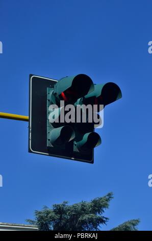 Traffic Lights / Signals partly showing Red colour, against Blue coloured sky during daytime, Rome, Italy, Europe - Stock Photo