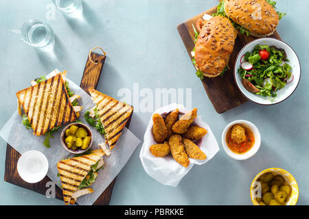 Grilled sandwich with nuggets, salad, sauce and pickled cucumbers on blue background top view - Stock Photo