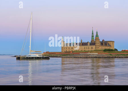 A catamaran for anchor at Kronborg Castle (a UNESCO World Heritage Site since 2000) at dusk in Helsingor, Denmark - Stock Photo