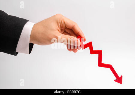A businessman's hand is holding a red arrow down on a white background. The concept of reducing costs and profits, falling living standards and prices - Stock Photo