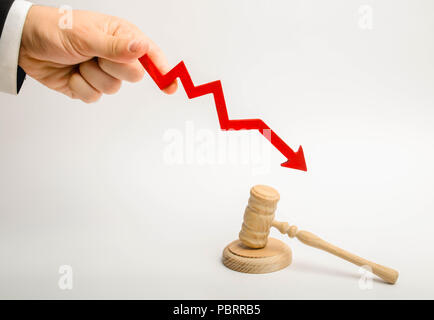 The hand holds the arrow down near the judge's hammer. The concept reduces the percentage of disclosure of criminal cases, lowering the percentage of  - Stock Photo