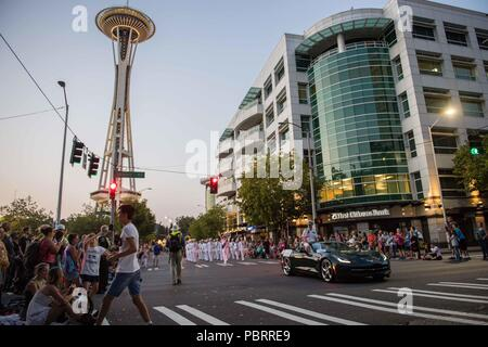 180728-N-DA737-0172 SEATTLE (May 28, 2018) Rear Adm. Scott Gray, commander, Navy Region Northwest, and the Navy Band Northwest marching band, participate in the Alaska Airlines Seafair Torchlight Parade in Seattle as part of the 69th annual Seafair Fleet Week. Seafair Fleet Week is an annual celebration of the sea services wherein Sailors, Marines and Coast Guard members from visiting U.S. Navy and Coast Guard ships and ships from Canada make the city a port of call. (U.S. Navy photo by Mass Communication Specialist 2nd Class Jonathan Jiang/Released) - Stock Photo