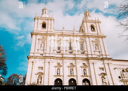 Facade of Monastery of Sao Vicente de Fora in Alfama, Lisbon against blue sky with white clouds. The monastery contains the royal pantheon of the Braganza monarchs of Portugal - Stock Photo