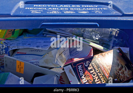 A large blue recylables container distributed by our city. Stamped on the lid is indicated all the variey of products that can be inserted and recyled - Stock Photo