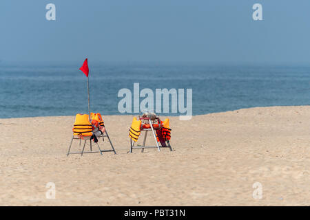 Stack of orange plastic chairs on an empty sandy beach - Stock Photo