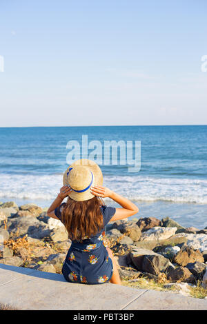 Beautiful girl in a hat sits near the sea on stones - Stock Photo