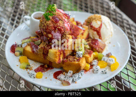 Dessert plate of Honey toast with ice cream Vanilla, mixed fresh sliced fruits, mango slices, kiwi, dragon fruit and whipped cream on metal table - Stock Photo