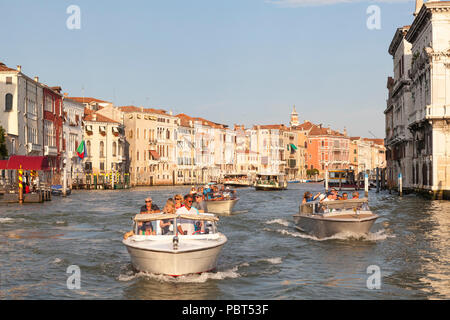Water taxis with tour groups on the Grand Canal at sunset, Venice, Veneto, Italy passing the historic palazzos, palaces of Cannaregio. Busy water traf - Stock Photo