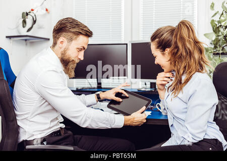 Image of happy young colleagues sitting in office coworking using digital tablet - Stock Photo