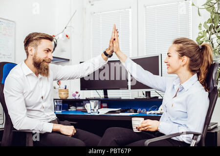 Happy caucasian colleagues giving high five celebrating good teamwork result or achievement in office, diverse motivated coworkers sharing business su - Stock Photo