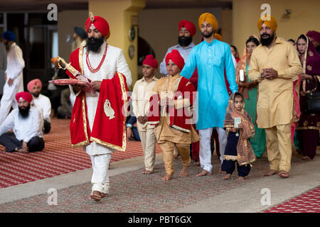 A Sikh groom, his little brother and others enter the temple for his wedding in Richmond Hill, Queens, New York. - Stock Photo