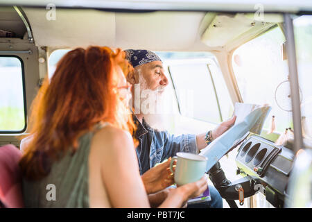 A trendy senior couple on vacation in a van - Stock Photo