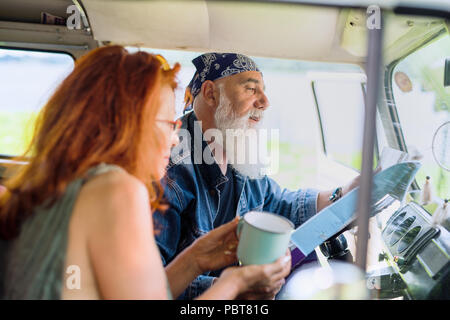 A hipster senior couple on vacation in a van - Stock Photo