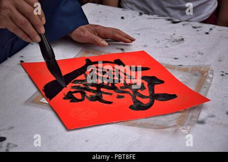 Chinese calligraphy written by an old man. This felicious wish for making money is often used during Spring Festival in China. A character translation - Stock Photo