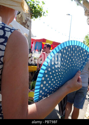 Woman fanning herself with a blue folding fan as she walks around a street market in The South of France - Stock Photo