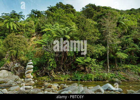 Cairn marking a stream crossing. Abel Tasman National Park, New Zealand - Stock Photo