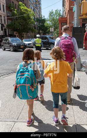 Man escorting young female students from school to home in New York USA - Stock Photo