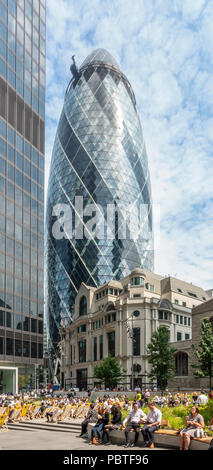 The Gherkin / 30 St Mary Axe, and St Helen's tower above Fitzwilliam House and local workers and visitors relaxing in St Helen's Square. - Stock Photo