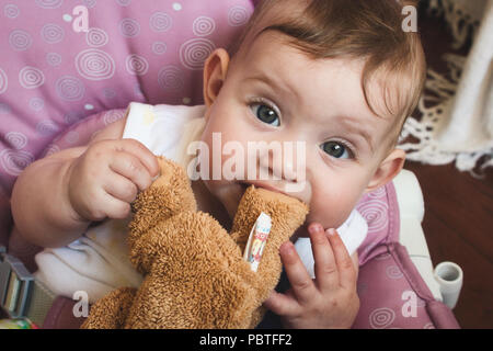 Cute baby girl playing with her brown teddy bear soft toy and chewing on the bear's foot - Stock Photo