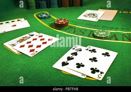Closeup of dealt cards and stacks of chips on a Blackjack table in a casino - Stock Photo