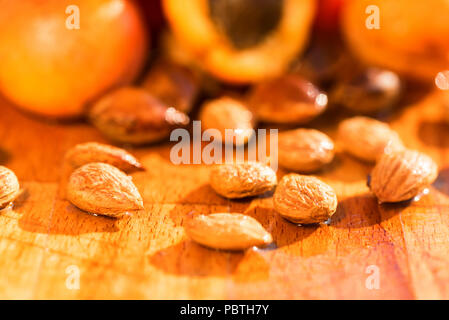 Fresh apricots and stones on wooden surface - Stock Photo
