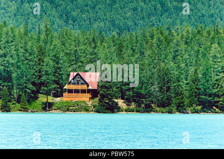 Wooden house near the blue lake in the dense forest among the trees. Tourist base in the Siberian taiga. Wooden frame house. Altai. Russia - Stock Photo