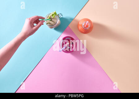 three colorful smoothies served in a jar and a woman's hand put a drinking straw on a colored paper background - Stock Photo