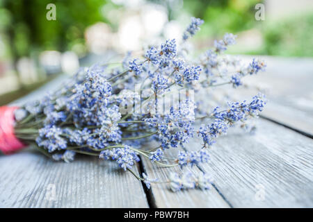 dried lavender flower over wooden rustic background on daylight, bunch of aromatic plant - Stock Photo