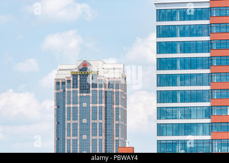 Raleigh, USA - May 13, 2018: Downtown North Carolina city skyscrapers, hotels during day with modern buildings, businesses, Wells Fargo Bank closeup - Stock Photo