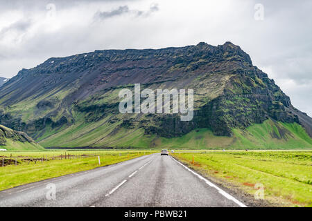 Iceland mountains landscape view of road trip, car, mountain cliff on cloudy day, south southern ring road or golden circle - Stock Photo