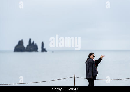 Vik, Iceland - June 14, 2018: Young asian woman tourist taking pictures photographing selfie with phone, ocean horizon, rock formations at Dyrholaey,  - Stock Photo