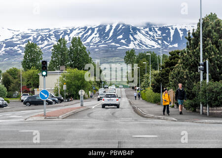 Akureyri, Iceland - June 17, 2018: Cityscape road in town village city with people locals or tourists couple walking on street sidewalk, view of snow  - Stock Photo