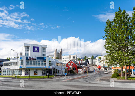 Akureyri, Iceland - June 17, 2018: Cityscape road in town village city with people, church, street sidewalk, view of snow mountain in summer - Stock Photo