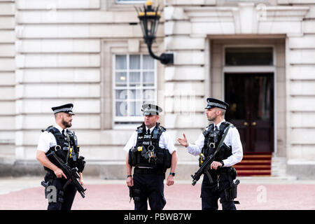 London, UK - June 21, 2018: Three English Royal security guards police officers with automatic weapons guns standing talking in front of Buckingham Pa - Stock Photo