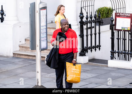 London, UK - June 22, 2018: Neighborhood district of South Kensington man carrying Sainsbury's grocery shopping bags waiting to cross street, bus stop - Stock Photo