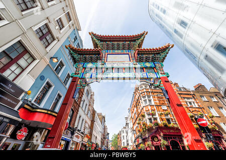 London, UK - June 24, 2018: Wide, low angle view looking up of Chinatown China town gate street road with nobody, downtown city, Chinese sign, red col - Stock Photo